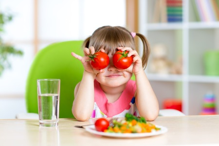 glass table: funny child little girl playing with vegetables Stock Photo