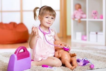 ragazza innamorata: La bambina gioca medico di controllo, baby doll paziente con il giocattolo stetoscopio