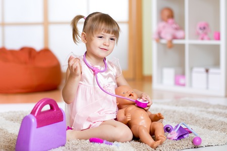 doc: Little girl plays doctor examining baby doll patient with toy stethoscope Stock Photo