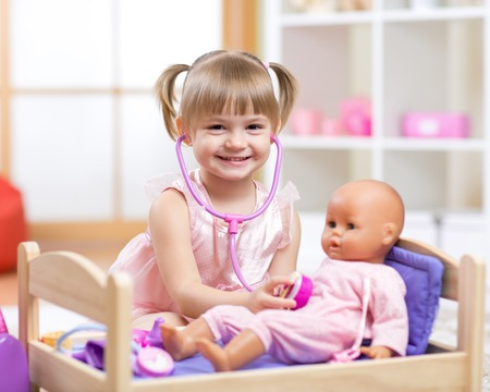 cute baby plays in doctor with toy doll and stethoscope