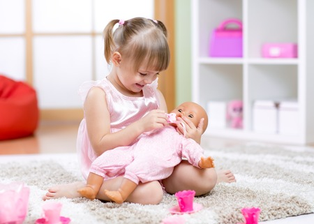 role play: Cheerful little girl playing with doll in preschool