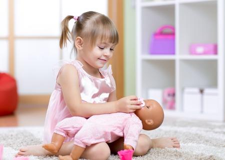 Belle fille de médecin enfant jouant avec une poupée Banque d'images