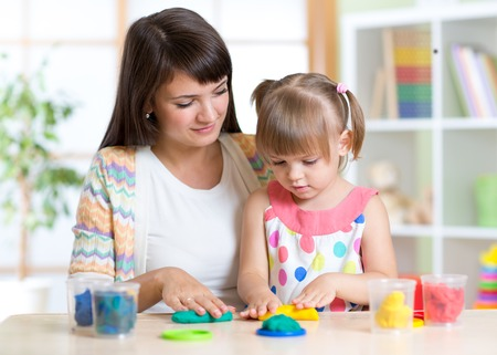 Young pretty woman and kid playing with colorful clay molding different shapes Imagens