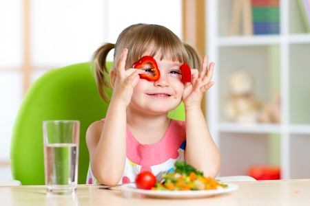 kid having fun with food vegetables in children room Stock Photo