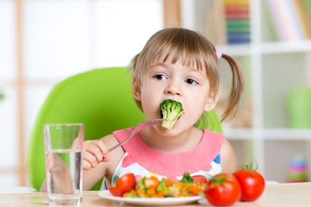 Enfant petite fille mange salade de légumes avec fork Banque d'images