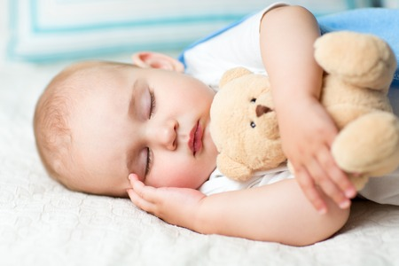 baby sleeping with fluffy toy on bed