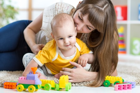baby toys: child boy and his mother playing together with toys at home
