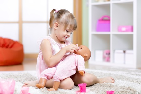 day care center: child girl playing with her baby-doll in day care center