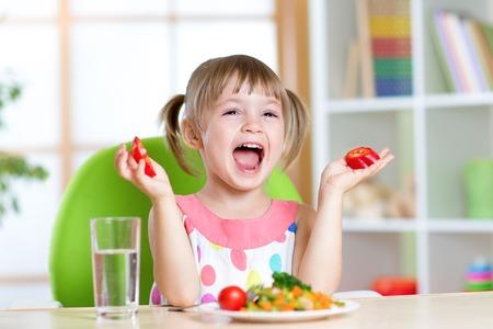 tomando agua: Chica niño comer alimentos vegetales saludable en el hogar o el jardín de infantes