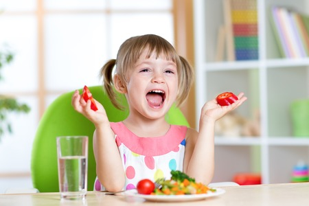 kid girl eating healthy vegetables food at home or kindergarten