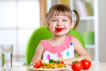 mignonne petite fille: funny girl d'enfant de manger des légumes sains à la maison
