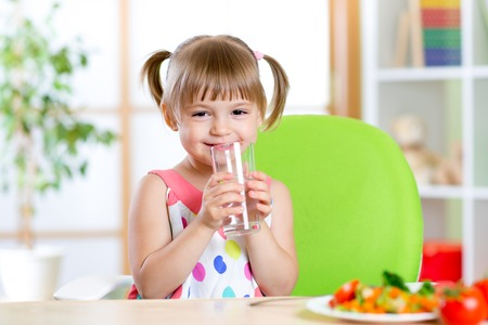 Smiling cute child girl holding glass of water at home