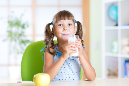 playful: child girl having breakfast: drinking a glass of milk