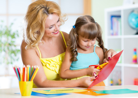 day care center: Happy woman teaching preschooler kid do craft items in day care center Stock Photo