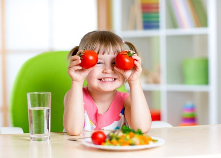 Child with tomatoes. Happy little girl with vegetables at home. Stock Photo