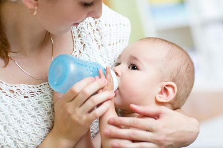 nursing bottle: Young mother at home feeding their baby with milk bottle, feeling proud