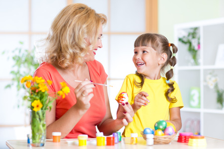 creative egg painting: Mother showing to her child daughter how to paint  Easter eggs