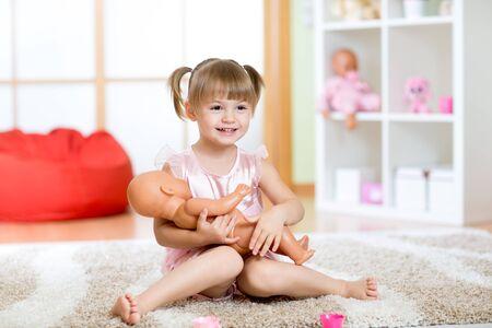 niñas jugando: Muchacha linda del niño sosteniendo y abrazando a su muñeca