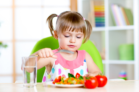 day care center: Kid eats fresh vegetables. Healthy eating for child.