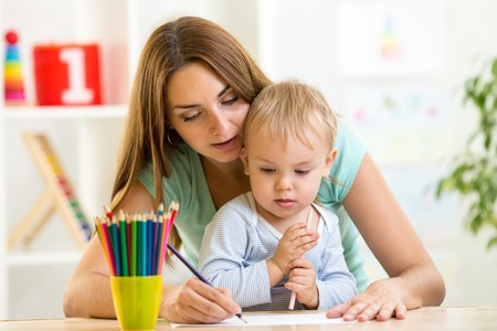 kindergarten education: happy family concept - mother and child boy drawing pencils