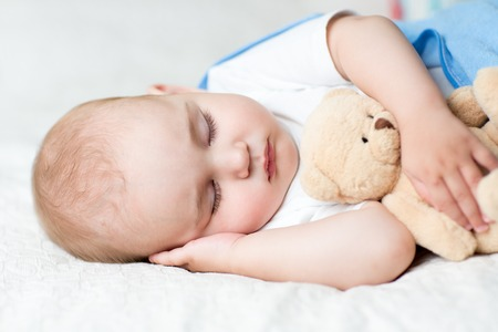 oversleep: Carefree sleep baby with soft toy on bed Stock Photo