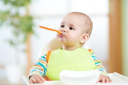 grappig kind met een lepel in de mond indoor Stockfoto