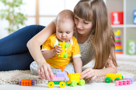 indoors: mother and baby boy play together indoors