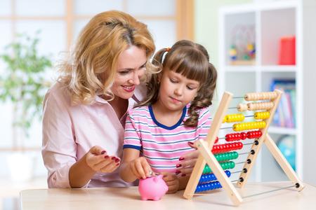 jolie petite fille: Mère et fille de mettre des pièces dans la tirelire. Enfant comptage et économiser de l'argent.