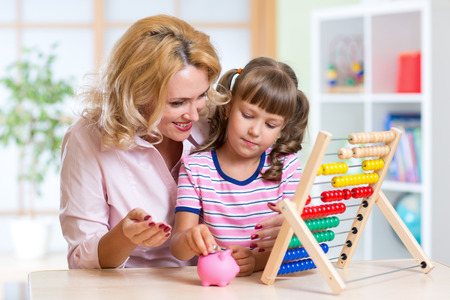 bank interior: Mother and daughter putting coins into piggy bank. Child counting and saving money. Stock Photo
