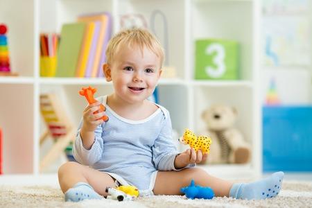 smart child boy plays animal toys sitting on floor Stock Photo