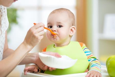 Mother feeding baby girl. Child sitting in hich chair in kitchen.