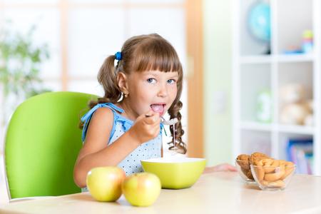 comiendo cereal: Chica niño comer alimentos saludables en guardería Foto de archivo
