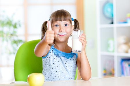 mleka: dziecko dziewczyna napojów mlecznych i pokazując kciuk w górę