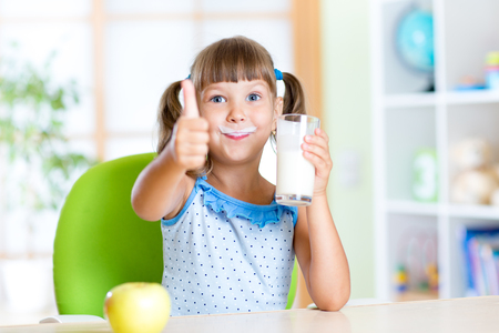 child girl drinks milk and showing thumb up Foto de archivo