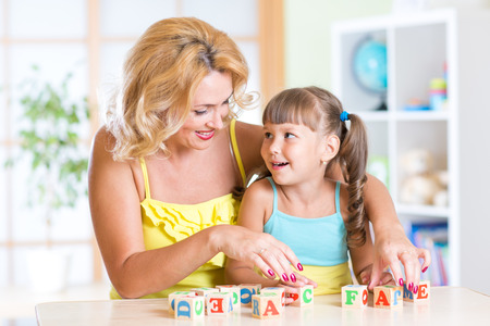 mum and daughter: kid plays building blocks with parent at home