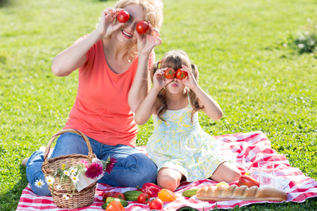 picnicking: Funny child girl and mother sitting outdoors and picnicking together Stock Photo