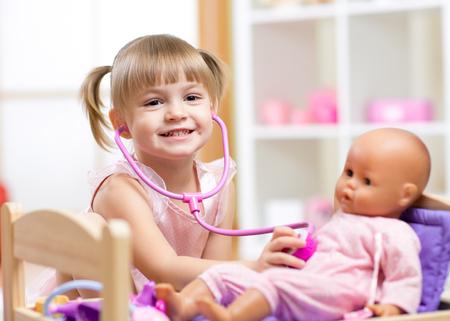 kinder: Chica ni�o que juega al doctor juego de rol examinating su mu�eca usando estetoscopio sentado en sala de juegos en el hogar, la escuela o el jard�n de infantes