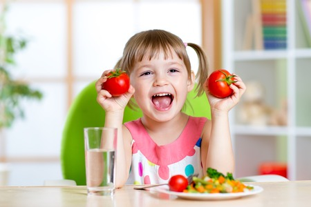 Portrait of happy child with vegetables sitting at table Stock Photo