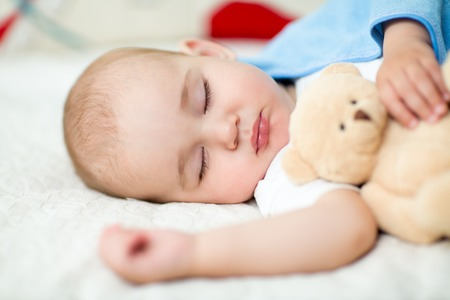 infant baby boy sleeping with plush toy