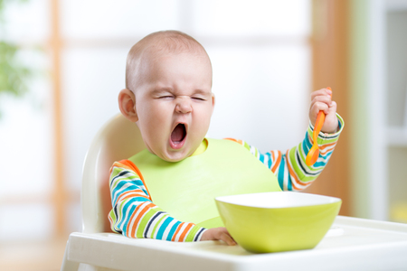 baby chair: funny kid boy eating healthy food indoors Stock Photo