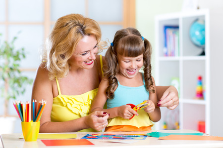 scissors cutting paper: Child girl with woman cutting out scissors paper in preschool Stock Photo