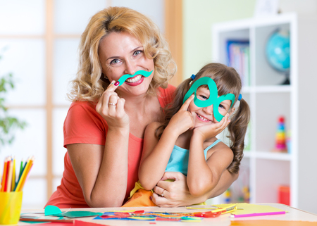 playschool: Kid girl with mother have a fun cutting out scissors paper in preschool Stock Photo