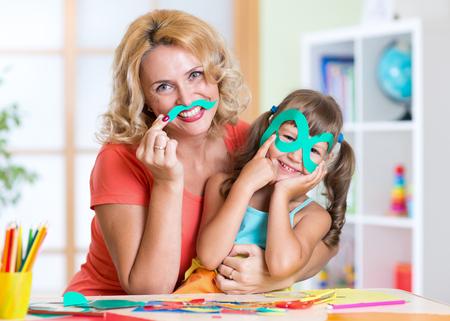 paper craft: muchacha niño con la madre tiene una diversión cortar papel tijera en preescolar Foto de archivo
