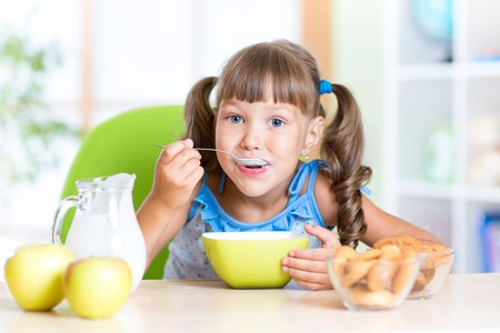 niños desayunando: linda niña niño comiendo cereales con leche en la guardería