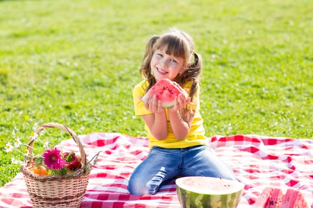 hold on: cute child girl eating watermelon on the grass in summer sunny day Stock Photo
