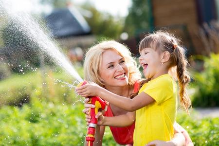 trabajando en casa: Feliz madre e hija niño que trabaja en el jardín