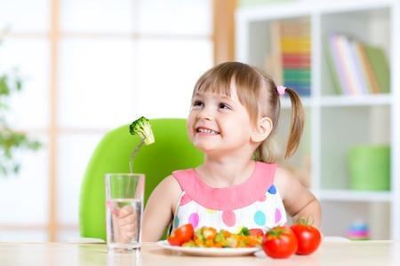 El cabrito come comida de verduras saludables en el hogar o cuidado de niños