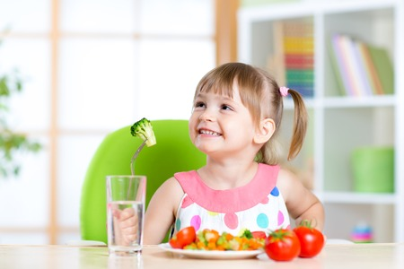 Kid eats healthy vegetables meal in home or nursery Standard-Bild