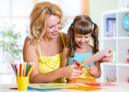 paper craft: La madre que enseña al niño preescolar hace artículos del arte. Concepto de bricolaje Foto de archivo