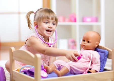 child care: Child in kindergarten. Kid in nursery school. Little girl playing doctor with doll